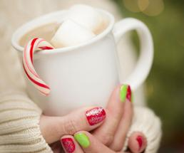 hands with red and green nails holding cocoa with candy cane