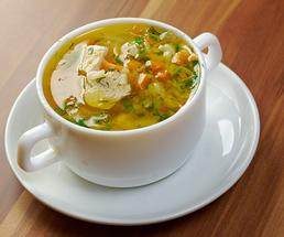 turkey soup in a small white cup and dish