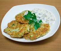 three potato pancakes on a white plate near white sauce
