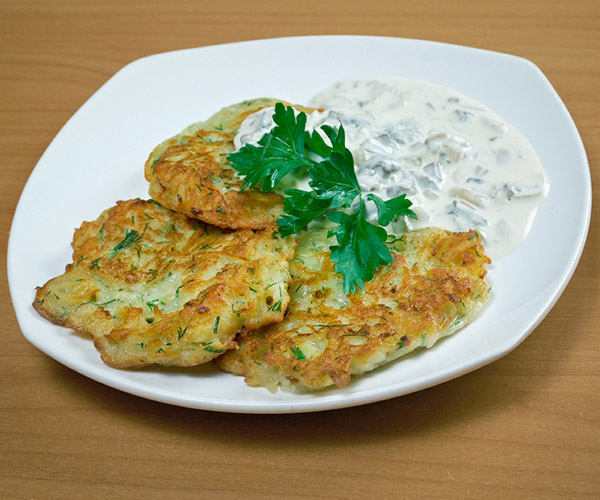 three potato pancakes on a white plate near white sauce