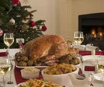 holiday turkey on a table with glasses of wine and other silverware and plates