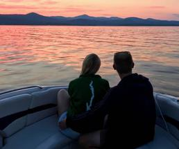 back of couple on a boat watching the sun set