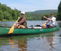 father and son paddling a green canoe