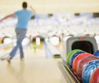 man throwing a bowling ball in bowling alley