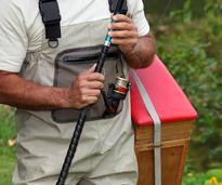 a man with fishing pole and gear