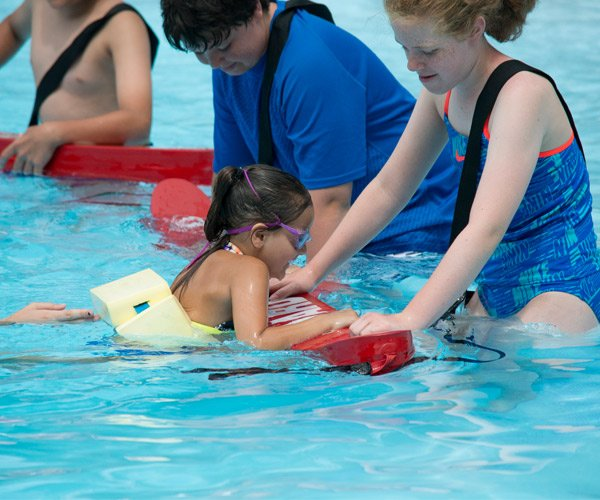 girl taking a swim lesson with a lifeguard