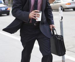 man walking holding coffee and a briefcase