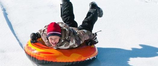 a boy snow tubing