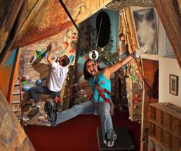 woman zip lining indoors near rock wall