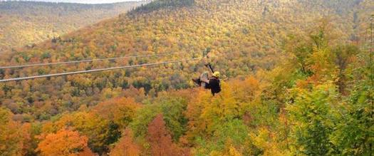 person ziplining in the fall