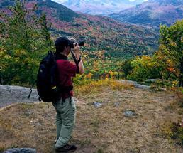 man on mountain in fall taking photos