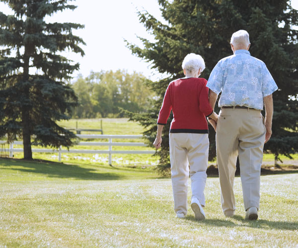 an older man and woman walking together holding hands