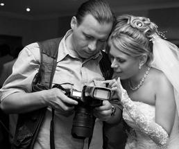 bride and wedding photographer looking at recent photo