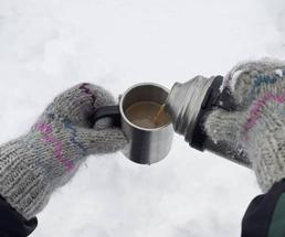 gloved hands pouring warm drink from thermos