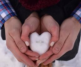 ring in snow heart held in couple's hands