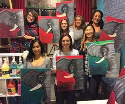 group of people holding up paintings indoors