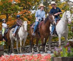 two adults and two kids horseback riding