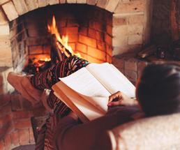 woman reading by the fire