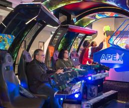 adults playing video games in arcade