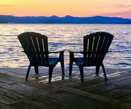 two Adirondack chairs by sunset