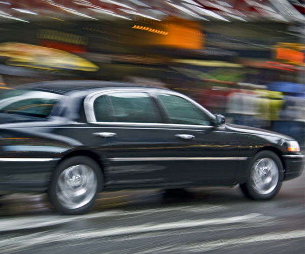 black sedan driving through a busy area