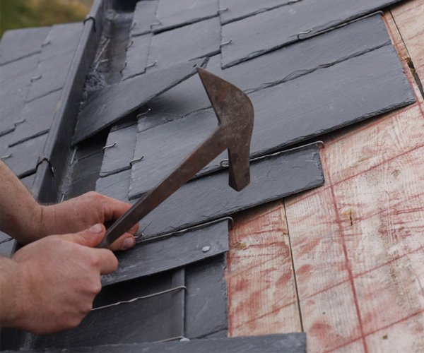 person installing a slate roof