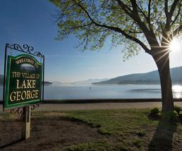 spring sun and lake george village sign