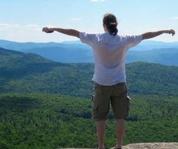 man at summit doing I'm King of the World pose