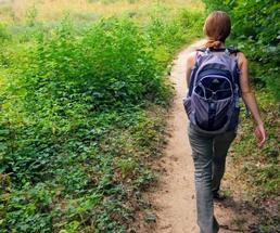 woman hikes with backpack on