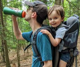 man drinking from water bottle, son on back
