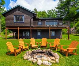 house in background, Adirondack chairs around fire pit