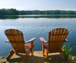 two Adirondack chairs in front of lake