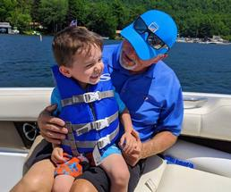 grandpa and grandson on a boat smiling