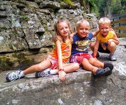 three kids on a rock