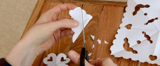 hands making paper snowflakes