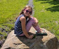 girl with sunglasses on rock