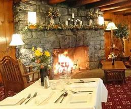 large rustic room with stone fireplace