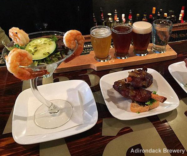 a beer sampler and two appetizers on a bar