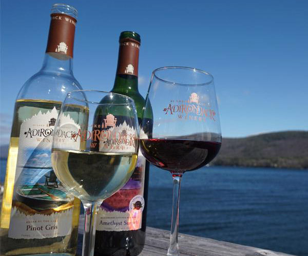 two bottles and two glasses of whine on a dock with the lake in the background