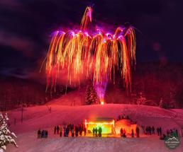 Pink and orange fireworks over an igloo with people watching