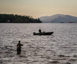person in water fishing, another person in boat