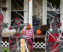 A house decorated with cobwebs and jack-o-laterns for Halloween.