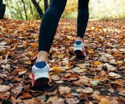 woman walking on fallen leaves