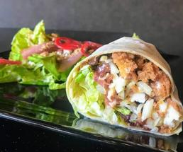 chicken wrap with salad in background