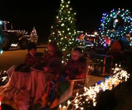 kids on a tractor with holiday lights
