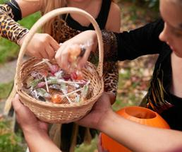 kids' hands reaching for Halloween candy from basket
