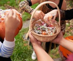 hands reach for candy in basket