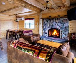 room in cabin with fire in fireplace