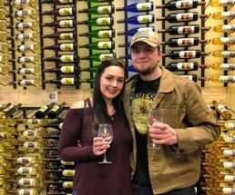 a couple standing in front of wine wall