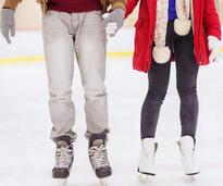 a couple holding hands and ice skating